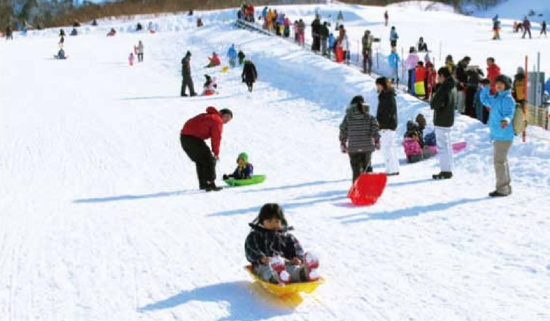 そり滑りを楽しむ家族連れ
